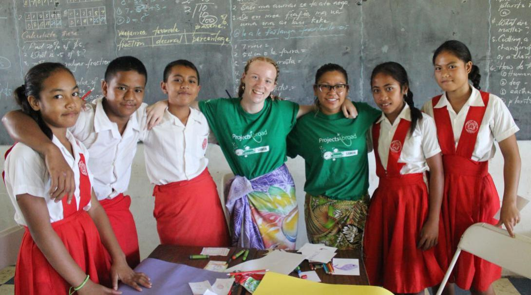 On a summer volunteer program abroad, a volunteer teacher takes a photo with her Samoan students.